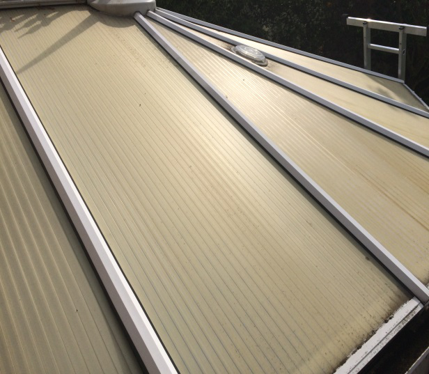 Before replacement: failed, dirty, discoloured roof panels